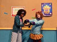 "(from l-r) Jori Jackson, playing Junie B. Jones' best friend, Grace, admires Junie B.'s new furry gloves. Mary McElree (right) plays Junie B. in Dallas Children's Theater's ""Junie B. Jones Is Not a Crook.'(Karen Almond)"
