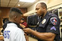 "<p>Arlington police Cpl. Damien Gary teaches <span style=""font-size: 1em; background-color: transparent;"">Isiah Austin </span><span style=""font-size: 1em; background-color: transparent;"">how to tie a necktie at a formalwear shop during an after-school program.</span></p>((Arlington Police Department))"