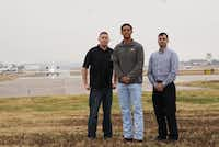 <p>Air traffic controller Marc Gough (left) alerted pilot Daniel Luna (center) and FAA inspector Cristóbal Diaz that smoke was spilling from the front of their plane during a flight. They're pictured at the north end of Addison Airport's single runway. (Lawrence Jenkins/Special Contributor)</p>