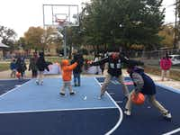 Officer Allison Brockford, who works in the Dallas Police Department's youth outreach unit, played basketball with children at the J.W. Ray park's new Dream Court in December.  (Named Rajwani/ The Dallas Morning News)(The Dallas Morning News)