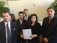 Angela Hunt, center, holds a copy of the Freedom of Information Act lawyers submitted during a press conference Sunday.(Sarah Mervosh/Staff)