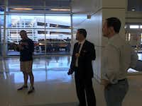 Lawyers Pete Schulte, left, Carlos Cortez, center and Perrin Fourmy pause while volunteering at D-FW International Airport Sunday.((Sarah Mervosh/Staff))