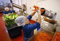 Marsala Giron loads a juicer with carrots to make Vim Vitae's natural, organic juices at their Dallas facility.(Tom Fox/Staff Photographer)