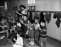 Kindergartners are led by their teacher as they sing an English folk song at an internment camp for Japanese-Americans in Tulelake, Calif. (1943 File Photo/The Associated Press)