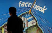 In this June 11, 2014, file photo, a man walks past a mural in an office on the Facebook campus in Menlo Park, Calif. (AP Photo/Jeff Chiu, File)(AP)