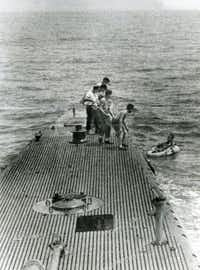 1944: Navy pilot George Bush (right) is pulled from the ocean by sailors onboard the Navy submarine USS Finback. After his plane was downed, he survived for hours in a small raft.(George Bush Presidential Library)