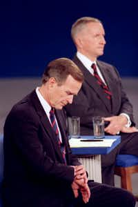1992:  In an indelible moment from the annals of televised presidential debates, President George H.W. Bush looks at his watch during a presidential debate at the University of Richmond. Independent candidate Ross Perot is at rear. Body language speaks volumes in televised debates, and classic moments sometimes have more to do with what the candidates do — or don't do —than what they say.(Ron Edmonds/AP)