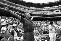 1994: Former Pres. George Bush acknowledges fans' cheers at The Ballpark in Arlington before the Texas Rangers played the Minnesota Twins. Son George W. Bush, Rangers' managing general partner, is seated at left, with wife Laura and daughter Jenna Bush at right.(David Woo/Staff photographer)
