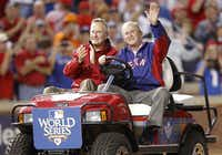 2010: Former Presidents George H.W. Bush and his son George W. Bush acknowledge the crowd before George W. Bush threw the ceremonial first pitch for Game 4 of the World Series between the San Francisco Giants and the Texas Rangers in Arlington.(Tom Fox/Staff Photographer)
