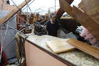 Gregory Rugon looks for his glasses at the spot where he took cover in his home after a tornado hit his Warren Drive home,  in the eastern part of New Orleans, Tuesday, Feb. 7, 2017. (Gerald Herbert/The Associated Press)