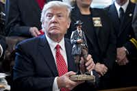 Trump holds up a statue he received as a gift while meeting with sheriffs in the Oval Office. (Andrew Harrer - Pool/Getty Images)