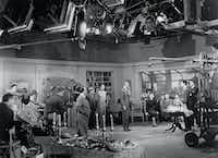 Director Alfred Hitchcock (center) rehearses star Jimmy Stewart and the cast as technicians look on during the making of <i>Rope</i>. Universal City Studios, 1948.