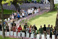 Participants walk past flags and signs planted in the grass honoring police officers and firefighters on the route of the Carry the Load fundraising walk last year at Reverchon Park in Dallas.(Ting Shen/Staff Photographer)