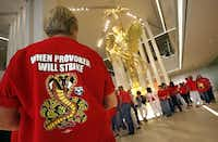 "Wearing red as a symbol of solidarity, members of the Communication Workers of America gathered peacefully Thursday around the ""Golden Boy"" statue in the lobby of AT&T headquarters in Dallas.  (Jim MahoneyThe Dallas Morning News)"