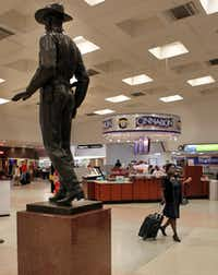A traveler heads to security at Dallas Love Field, and past the famous Texas Ranger statue (and a Cinnabon eatery) inside the main terminal at Dallas Love Field on April 21, 2010. (John F. Rhodes / The Dallas Morning News)