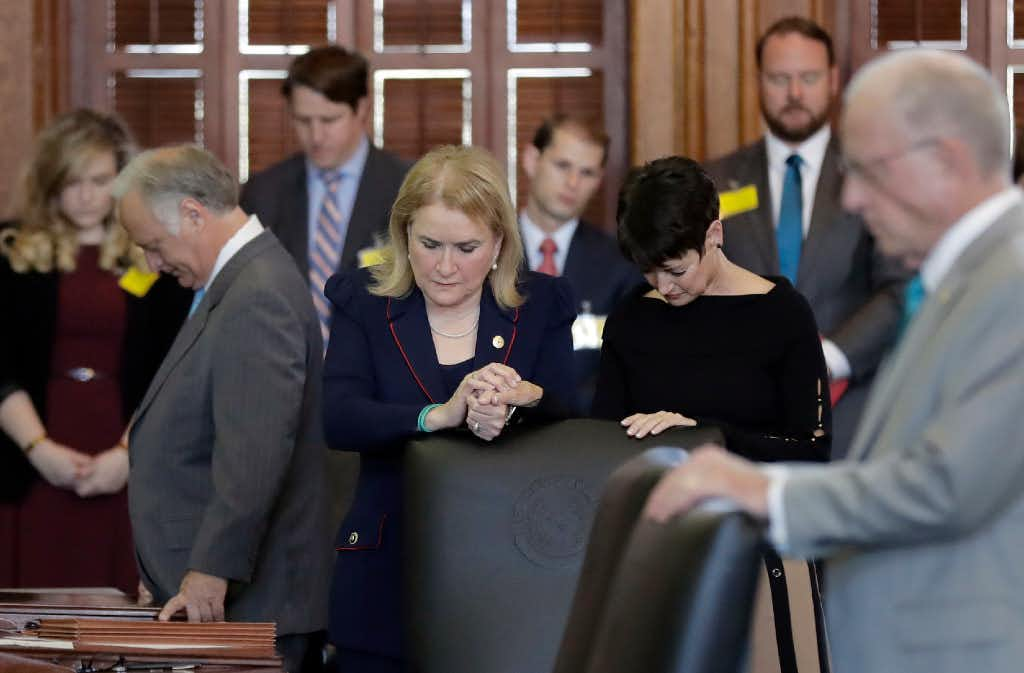 State Sen. Sylvia Garcia, D-Houston, and Sen. Donna Campbell, R-New Braunfels, joined hands during the opening prayer in the Senate Chamber at the Texas Capitol on Tuesday, Feb. 7, 2017, in Austin. (Eric Gay/The Associated Press)