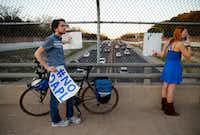 Dakota Access pipeline protesters Tim McCarthy and Desiree Graham held up signs over the Dallas North Tollway last week as they marched to the home of Energy Transfer Partners CEO Kelcy Warren. (Tom Fox/Staff Photographer)