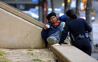 Senior Dallas police officer S. Ortega de King helps a homeless man understand he can not lay along the sidewalk. She did not write him a ticket or arrest him. Dallas police are targeting the area including City Hall and the J. Erik Jonsson Central Library for increased enforcement -mainly the homeless. They are ticketed for violations, such as obstruction of a public sidewalk, urination in public and public intoxication. Large numbers of homeless have been a problem in that area for quite some time.(RICHARD MICHAEL PRUITT)