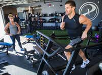 Paradigm Gym owner Brian Casad works out on a Matrix machine while his sister, co-owner and general manager Kelli Casad watches.<div><br></div>((Ashley Landis/Staff Photographer))