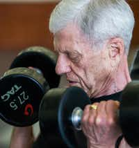 Bill Vick, who has pulmonary fibrosis, lifts weights at Carpenter Park Recreation Center in Plano. The disease interferes with a person's ability to breathe.(Ashley Landis/Staff Photographer)