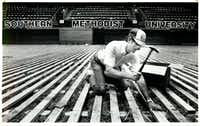 "Original caption (revised to add date and city): ""Wayne Smith, of Trinity Floor, hammers nails into the base of the new floor being installed in Moody Coliseum at SMU in Dallas August 18, 1986. The work was started two weeks ago and will continue for another month and a half."" ((Paula Nelson/Staff Photographer))"