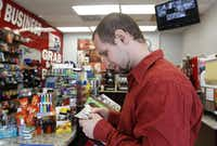 Charles Morehouse, 32, looks at a $100 bill after cashing a check at a gas station following his discharge after serving a 15-year sentence in Huntsville, Texas on Aug. 31, 2015. (Rose Baca/The Dallas Morning News)