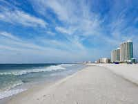 An expanse of fluffy, bright white sand makes Alabama's 32 miles of beaches alluring. This section of Orange Beach is lined with tall condos. ((Helen Anders))