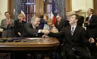 Texas Gov. Greg Abbott, front left, shakes hands with Zachariah Moccia, right, who has dravet syndrome, after he signed SB 339, a bill allowing the medical use of low-THC cannabis, into law at the Texas Capitol June 1, 2015 in Austin.(Eric Gay/AP)