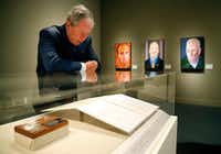 Former President George W. Bush reads one of the veteran letters on display of 'Portraits of Courage, A Commander In Chief 's Tribute To America's Warriors' (Tom Fox/The Dallas Morning News)