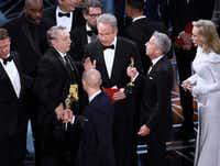 "Warren Beatty, center, discusses the results of the award for best picture with Academy of Motion Pictures Arts and Sciences officials and producers from ""La La Land"" at the Oscars on Sunday. Chris Pizzello/Invision/AP"