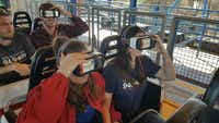 Staff members of 94.9 KLTY-FM adjust their VR goggles before riding the Galactic Attack at Six Flags Over Texas. (Tommy Noel/Staff photographer)