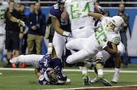 Oregon running back Tony Brooks-James (20) breaks the grasp of TCU defensive end Tipa Galeai (47) to score a touchdown during the first half of the Alamo Bowl on Jan. 2, 2016, in San Antonio. (AP Photo/Eric Gay)