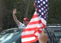 President Donald Trump waves from his vehicle after it stopped close to supporters near his Mar-a-Lago resort home on Saturday in West Palm Beach, Fla. President Trump spent part of the weekend at the house. ((Joe Raedle/Getty Images))