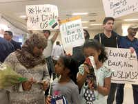 Family members whose grandmother from Sudan is being held at Dallas-Fort Worth International Airport await news of her status while joined by protestors Saturday, Jan. 28, 2017. (Jae S. Lee/The Dallas Morning News)