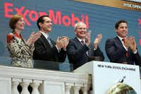 FILE - In this Wednesday, March 1, 2017, file photo, Exxon Mobil Corporation Chairman & CEO Darren Woods, third from left, joins the applause during opening bell ceremonies at the New York Stock Exchange. Woods succeeded Rex Tillerson, following Tillerson's nomination by President Donald Trump to be the next United States Secretary of State. Woods is a veteran of the more cautious refining side of the oil business who is likely to focus relentlessly on controlling costs. (AP Photo/Richard Drew, File)AP