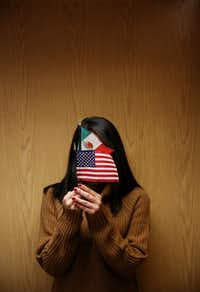 Diana is an immigrant from Mexico. She has Deferred Action for Childhood Arrivals, which stops a potential deportation and provides her a work permit. Diana wants her face hidden but not the flags of the countries she loves. (Andy Jacobsohn/The Dallas Morning News)