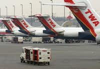 A Trans World Airline baggage cart crosses the tarmac behind a line of TWA jets Monday, Jan. 8, 2001 at Lambert International Airport, TWA's main hub, in St. Louis.  (AP Photo/Tom Gannam) AP