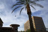 A passenger jet makes an approach to Sky Harbor International Airport over the US Airways headquarters building in Phoenix, AZ, Monday, December 2, 2013. US Airways will merge into the new American Airlines Group next week. (Tom Fox/The Dallas Morning News)Staff Photographer