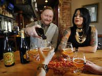 Hugh Morris pours a glass of Wicked Weed barrel-aged craft brew as he shares a bottle with Lisa Smith (right) and friends at The Bearded Lady. (Tom Fox/The Dallas Morning News)