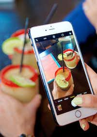 Stephanie Campos uses her phone to photograph her margarita at Urban Taco to share with her thousands of followers on social media.((Brandon Wade/Special Contributor))