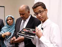 Ahmed Mohamed shows the clock he built in a school pencil box while standing with his parents, Muna Ibrahim and Mohamed Elhassan, after a news conference in Dallas on Aug. 8, 2016.((File Photo/David Woo))