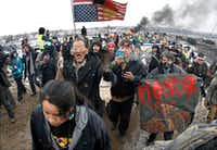 FILE - In this  Feb. 22, 2017, file photo, a large crowd representing a majority of the remaining Dakota Access Pipeline protesters march out of the Oceti Sakowin camp before the 2 p.m. local time deadline set for evacuation of the camp mandated by the U.S. Army Corps of Engineers near Cannon Ball, N.D. (Mike McCleary/The Bismarck Tribune via AP, File)