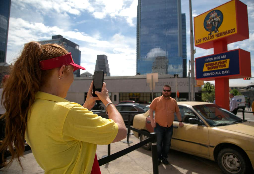 "On March 10, 2017, a ""Breaking Bad"" fan takes a picture in front of the Los Pollos Hermanos sign, which opened as a popup restaurant during South by Southwest. The fast food chain, which is featured in ""Breaking Bad"" and ""Better Call Saul"" is hosted by AMC during the festival. (Reshma Kirpalani/Austin American-Statesman/TNS)(TNS)"