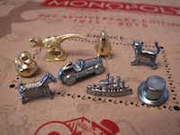 This March 15, 2017 photo shows the eight game tokens that will be included in upcoming versions of the Monopoly board game, in Atlantic City, N.J. Hasbro Inc. revealed the results of voting on Friday, March 17, 2017. Leaving the game will be the boot, wheelbarrow and thimble tokens, replaced by a ducky, T-Rex dinosaur and a penguin. (AP Photo/Wayne Parry)AP