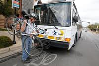 An Arlington MAX bus picks up John Smith and his bicycle at the College Park stop in Arlington on March 16. ((Nathan Hunsinger/The Dallas Morning News))