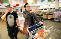 Feng and Brewer stroll one of Jusgo's produce aisles.(Rose Baca/Staff Photographer)