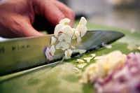 Barsotti slices garlic and red onion. (Tom Fox/Staff Photographer)