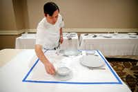 Ehlert gauges the space required for four place settings by laying pieces inside a 36-inch square taped off on a tablecloth. (Tom Fox/The Dallas Morning News)