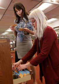 Sultana Vest (left) and library associate Catherine Gilman thumb through the new seed library program at the Dallas Public Library downtown. (Jason Janik/Special Contributor)