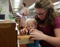 Roland Upchurch, 2, and Jeneva Upchurch browse the new seed library program at the Dallas Public Library downtown. (Jason Janik/Special Contributor)